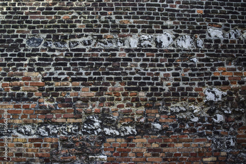 Poster Brick wall Background, texture: consists of a wall of red and blackened from old age brick interspersed with white and black stones