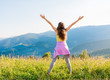 sporty young woman cheering open arms at mountain peak