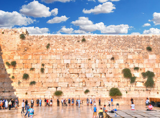 JERUSALEM, ISRAEL - HDR(high dynamic range) image - People visiting and praying at the Western Wall in cloudy blue sky.