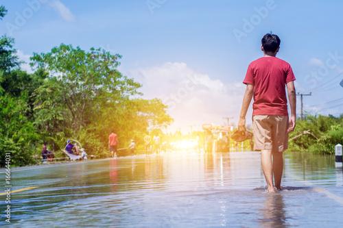 Plakat młody człowiek przechodzi przez powódź bosymi stopami.