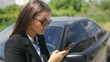 Side-closeup portrait of young upset businessgirl staying on countryside road, using smartphone for calling help evacuator evacuating repair