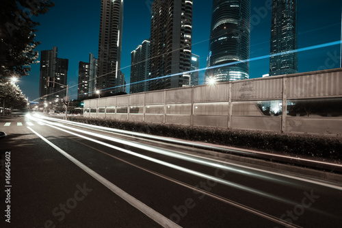 Empty road surface with city landmark buildings of night Poster