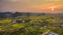Aerial View Of A Village Surrounded By Padi Fields And Hills Against Setting Sun In Guanxi, China