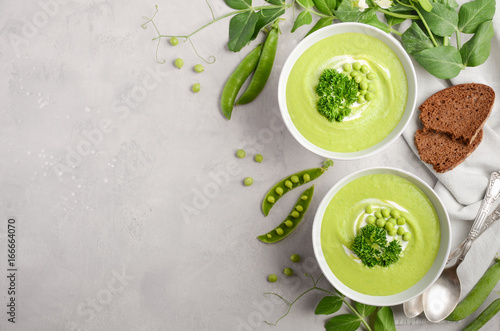 Fotografia Green pea soup in bowls on grey concrete or stone background, top view, copy spa