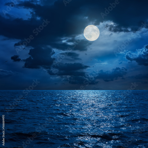 Poster Nuit full moon in clouds over sea in night