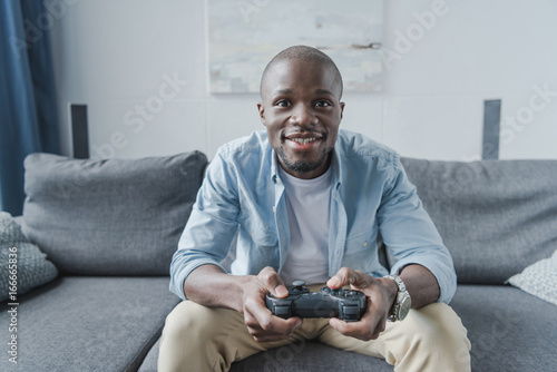 Photo  African american man playing with joystick