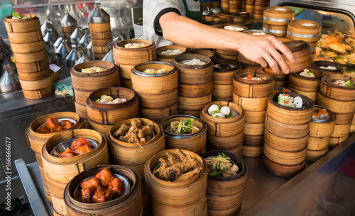 Hand of chef picked up a dim sum are steaming on the stove  Chinese restaurant that is popular in Hong Kong Canvas Print