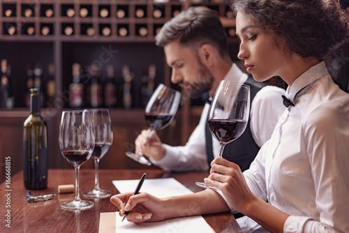 Fototapeta Sommeliers tasting wine in cellar
