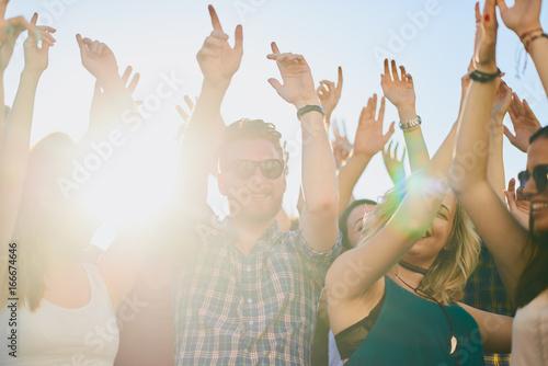 Papiers peints Magasin de musique Group of people dancing at summer festival, hands raised