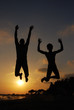 Father and son jumping on beach at sunset. Happy family on the sea. Summer vacation concept