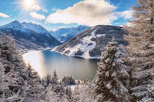 Poster Gris Lake and mountain range under cloudy sky with sun near Kaprun, Austria.