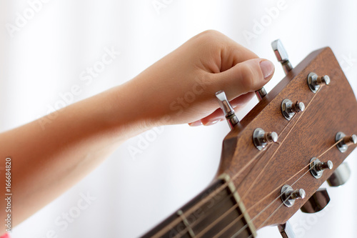 Photo Photo of girl's hand tuning acoustic guitar, close-up