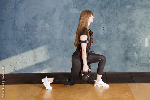 Fototapety, obrazy: the young woman in a suit for EMS of a training squats with weights. Fit girl exercise in the gym..