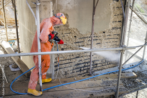 Worker in orange protective suit cleans corrosion damaged
