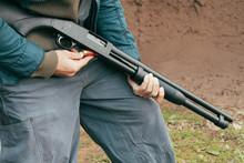 A Man Loading A 12 Bore Cartridge In A Pump Action Shotgun
