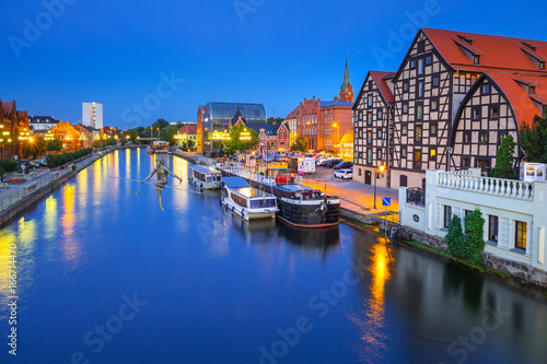 Architecture of Bydgoszcz city with reflection in Brda river at night, Poland
