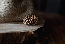 Pinecone Sits On Wood Disc By Burlap Fabric