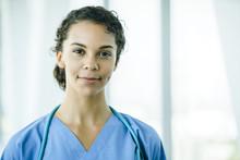 Portrait Of Confident, Happy Female Nurse In Hospital Hallway