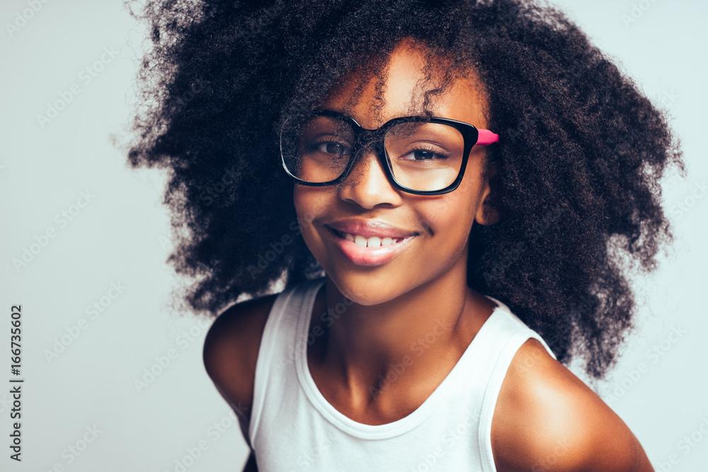 Fototapety, obrazy: Cute little African girl wearing glasses against a gray backgrou
