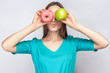 Beautiful young woman with freckles in green dress, holding before her eyes green apple and pink donut and kissing. studio shot on light gray background.