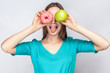 Beautiful young woman with freckles in green dress, holding before her eyes green apple and pink donut and shows tongue. studio shot on light gray background.