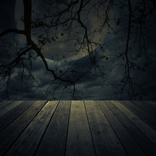 Old Wooden Table Over Dead Tree, Moon And Spooky Cloudy Sky, Halloween Background
