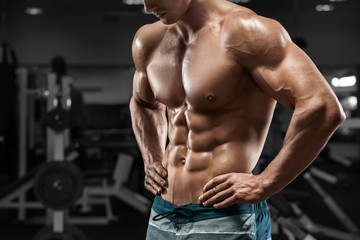 Fototapeta na wymiar Muscular man abs in gym, shaped abdominal. Strong male naked torso, working out