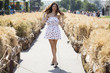 Young beautiful brunette woman in white dress walking on the street
