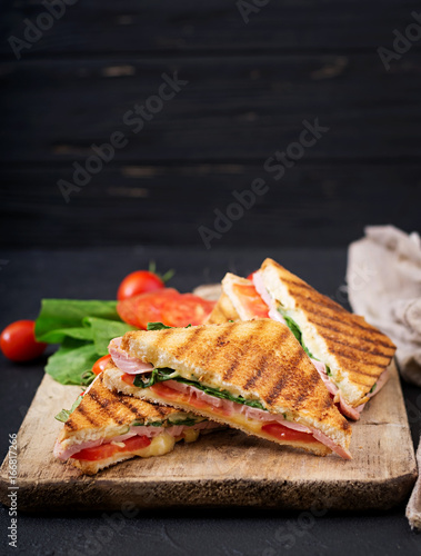 Club sandwich panini with ham, tomato, cheese and basil.