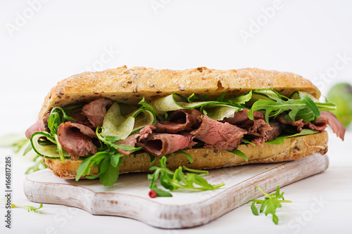 Staande foto Snack Sandwich of whole wheat bread with roast beef, cucumber and arugula.