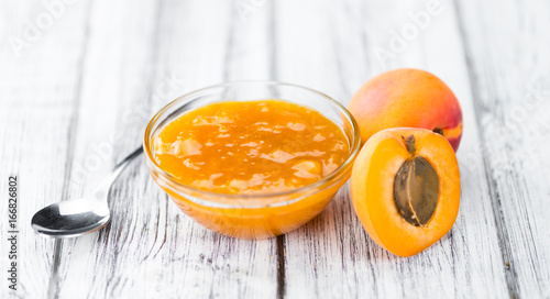 Portion of Apricot Jam on wooden background (selective focus)