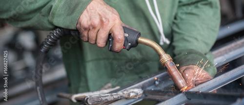 Fotobehang Fontaine Industrial worker welding the steel structure in the workshop