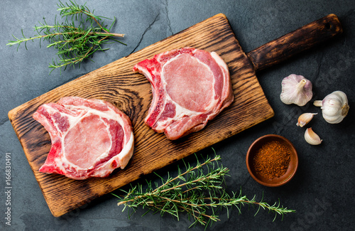 Photo  Raw pork cutlet chop for fry on pan with herbs, garlic on wooden boards, slate g