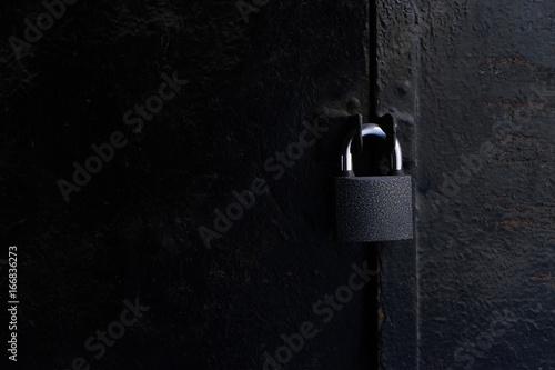 Photographie  black padlock on rusty metal door with copy space