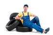 Service worker in blue uniform sitting on tires