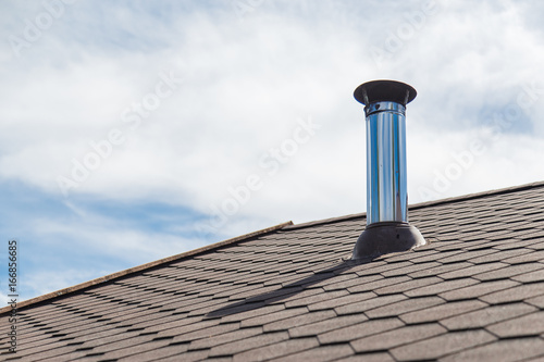 Chimney pipe from stainless steel on the roof of the house Fototapet