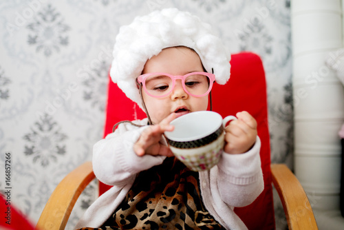 Beautiful baby girl is holding an empty cup of coffee and sitting in a chair. & Beautiful baby girl is holding an empty cup of coffee and sitting in ...