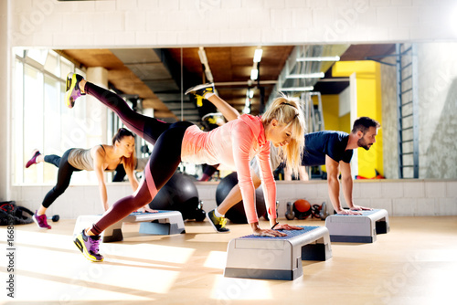 Photo Group of flexible people working out with steppers in gym.
