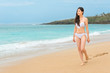 asian young bikini woman barefoot on beach walking