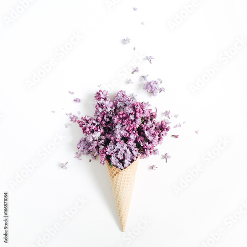 Staande foto Lilac Waffle cone with lilac flower bouquet on white background. Flat lay, top view floral background.