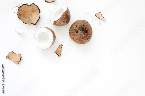 Cracked coconut on white background. Flat lat, top view