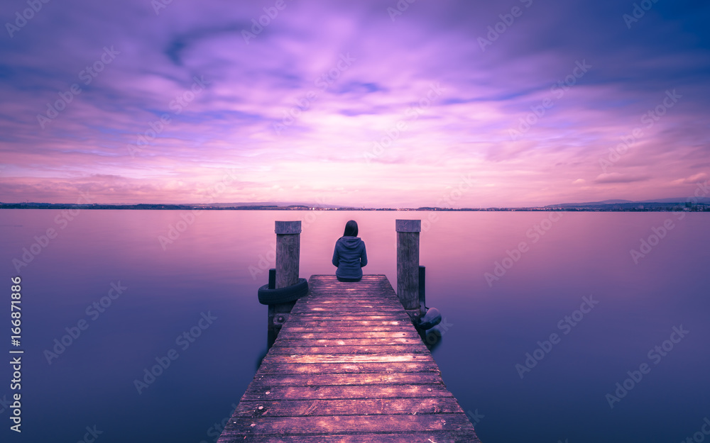 Fototapeta Mystical world. A lone figure on the pier of the lake. Long exposure.