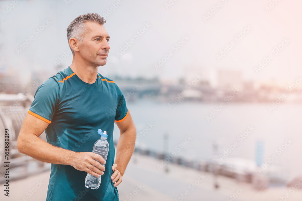 Fototapety, obrazy: Portrait of healthy athletic middle aged man with fit body holding bottle of refreshing water, resting after workout or running. on the riverside. vintage color