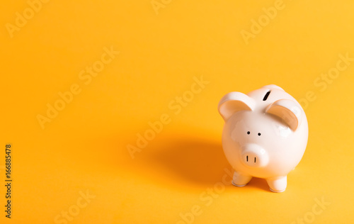Foto White piggy bank on yellow