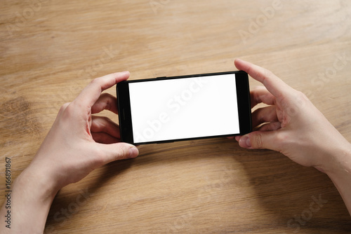 young man hands holding smartphone with blank white screen