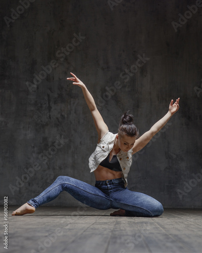 tancerka-z-niebieskich-spodniach-z-rozlozonymi-rekoma-na-ciemnym-tle