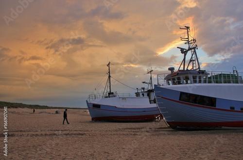 Staande foto Scandinavië Moody sky over fishing boats at the Thorup Strand, Denmark.
