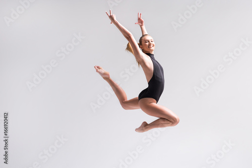 Spoed Fotobehang Gymnastiek Joyful young woman practicing rhythmic gymnastics workout