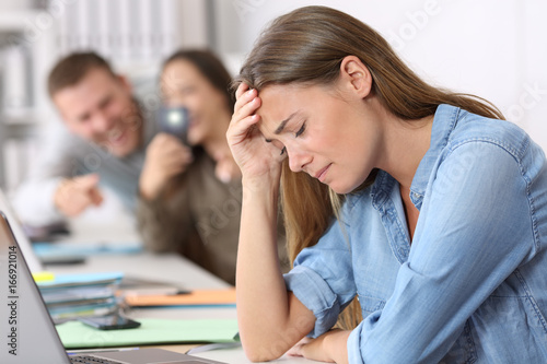 Cyber bullying victim being photographed at office Canvas Print