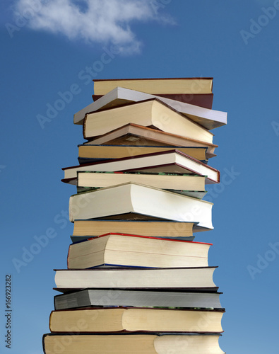 Stack of books on blue sky background Wallpaper Mural
